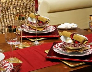 Christmas day table set with plates, cutlery, crockery and glassware