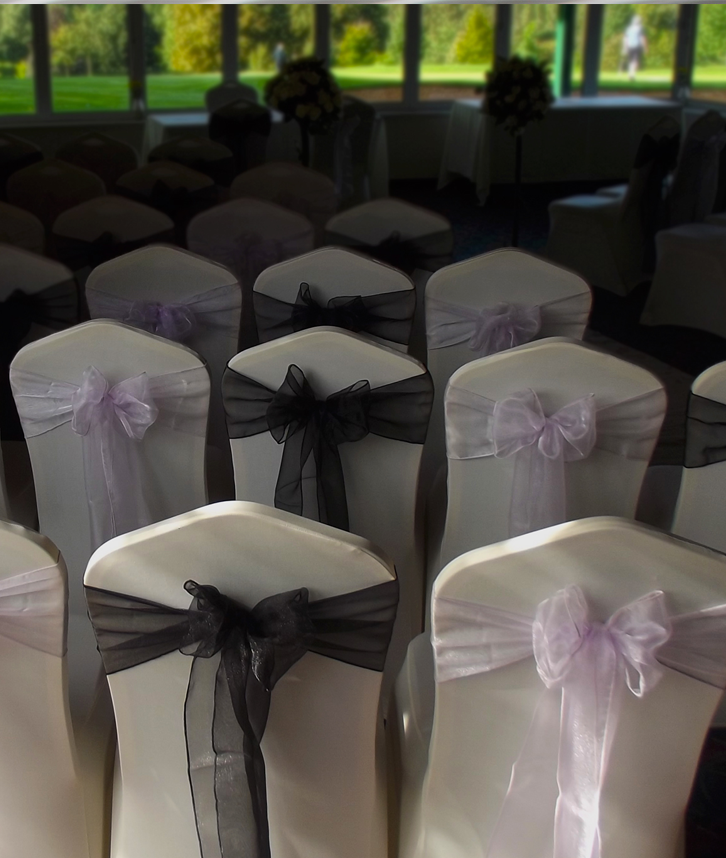 An image of multiple banquet style chairs complete with chair covers and black and lilac sashes.
