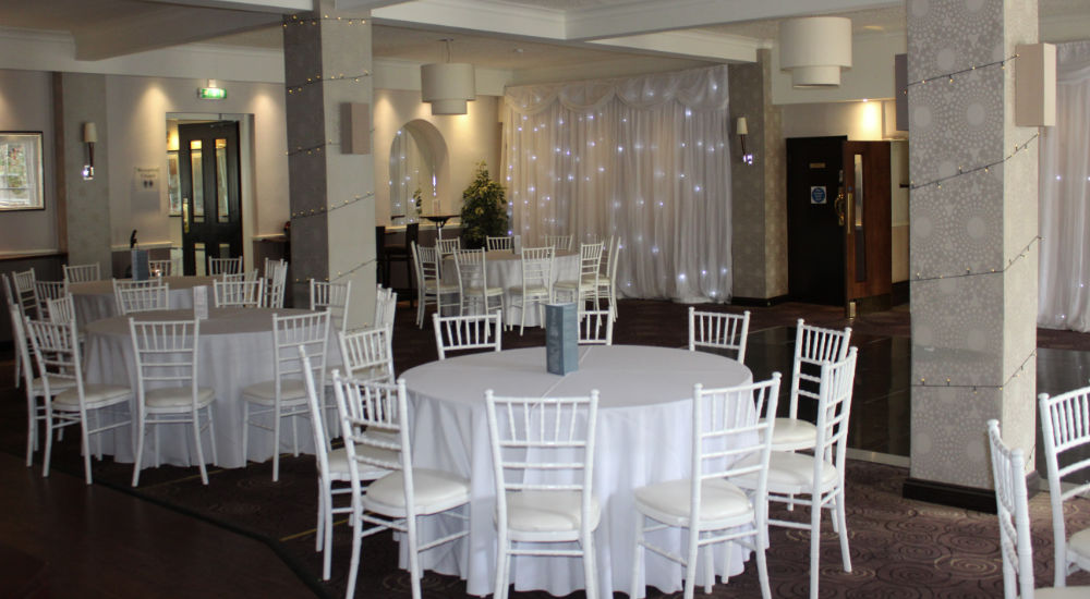 An image of a wedding reception table setup whih eatures round tables and wooden chairs that have been hired by Solid State UK.