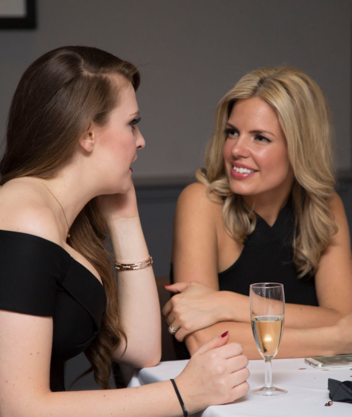 An image of two ladies talking at a table, at a party that has put out together by Solid State UK.
