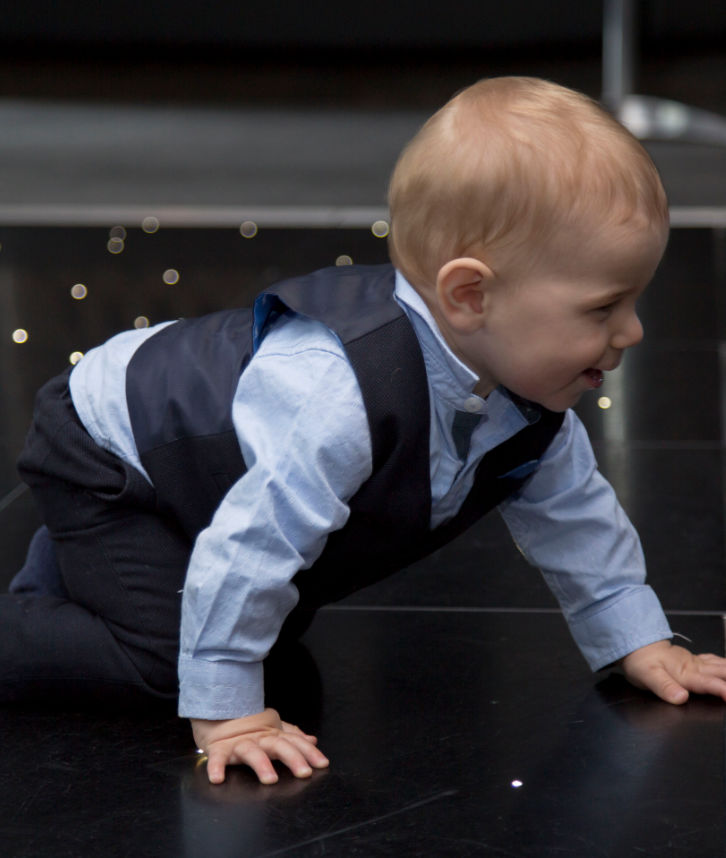 An image of a toddler crawling across a stage floor that has been hired by Solid State UK for a party.