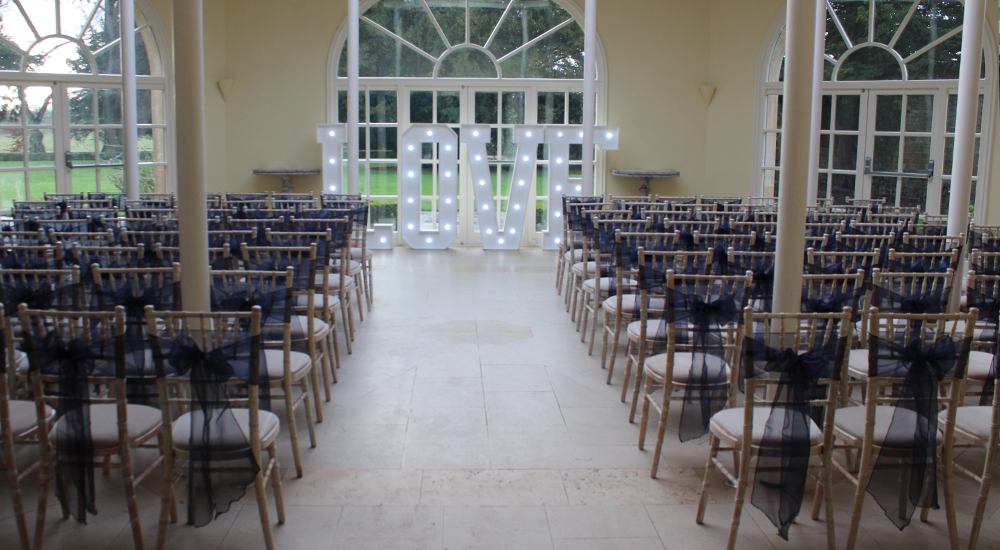 An image of several limewash Chiavari Chairs, complete with black chair sashes at a wedding venue.