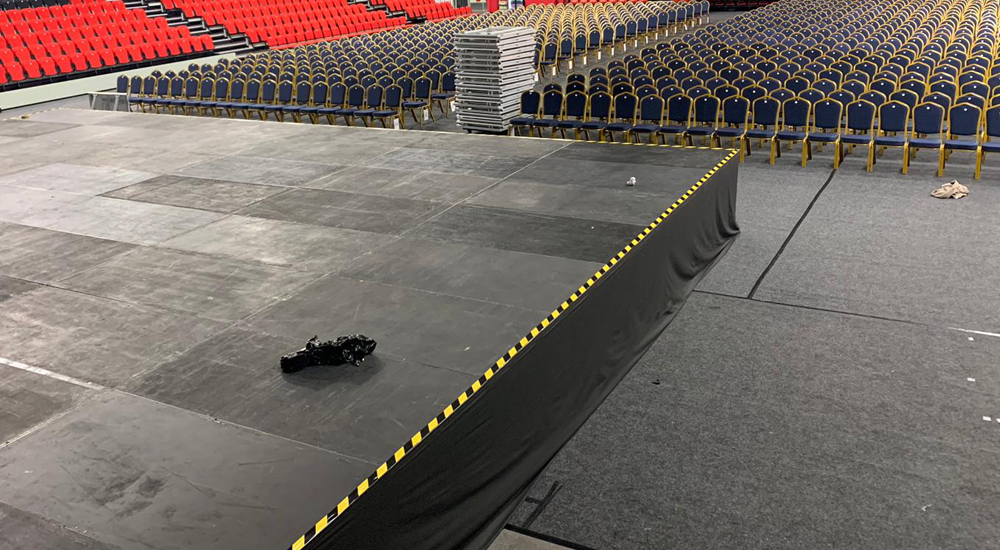 An image of a black stage being used in a hall and hired by Solid State UK.