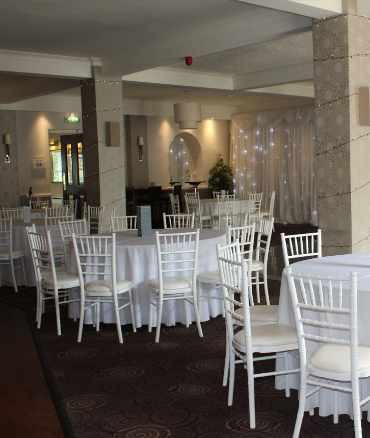 An image of round tables at a wedding venue, surrounded by white chiavari chairs.