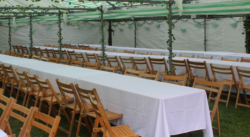 An image of wooden folding chairs placed around tables at a venue by Solid State UK.