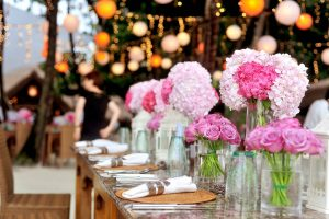 An image showing a wedding reception with pink flowers in the foreground on a wedding table with an out of focus image of a dance floor and lights in the background.