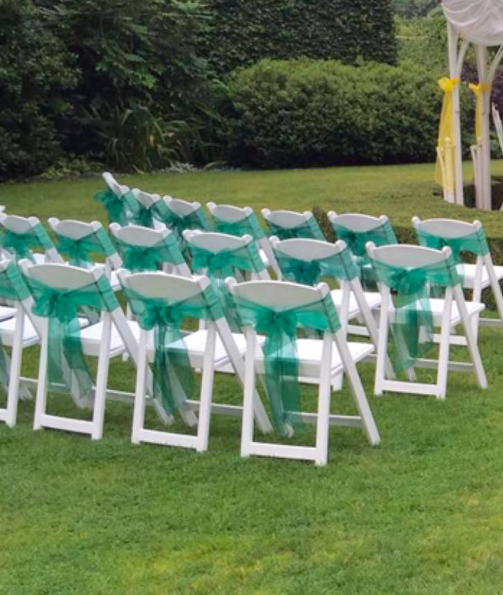 An image of folding chairs with a green ribbon tied around them for an outdoor wedding.