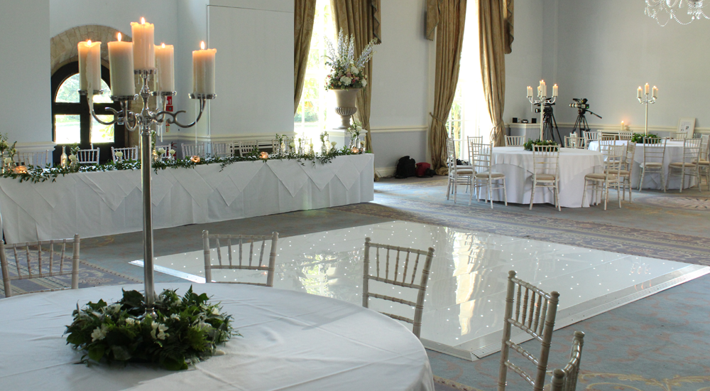 An image of a white dance floor with LED lighting in a formal wedding reception.