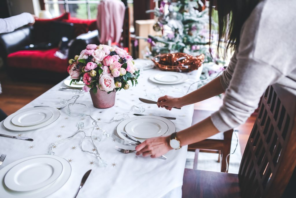 An image of a woman setting a guest table in a wedding reception venue.