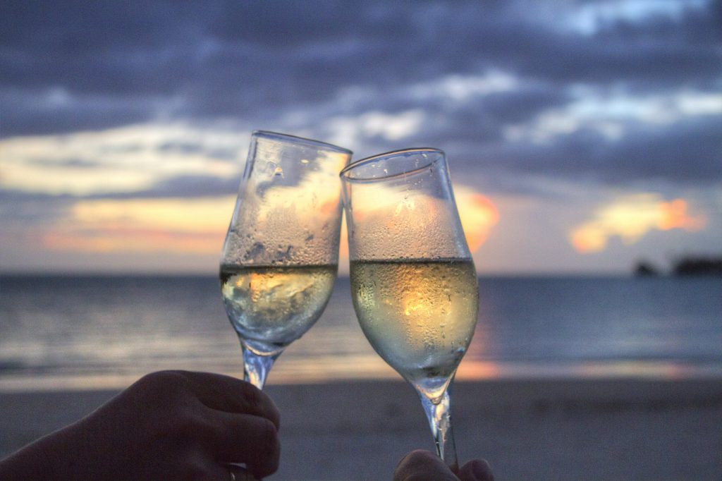 An image of two people toasting champagne glasses on the beach.