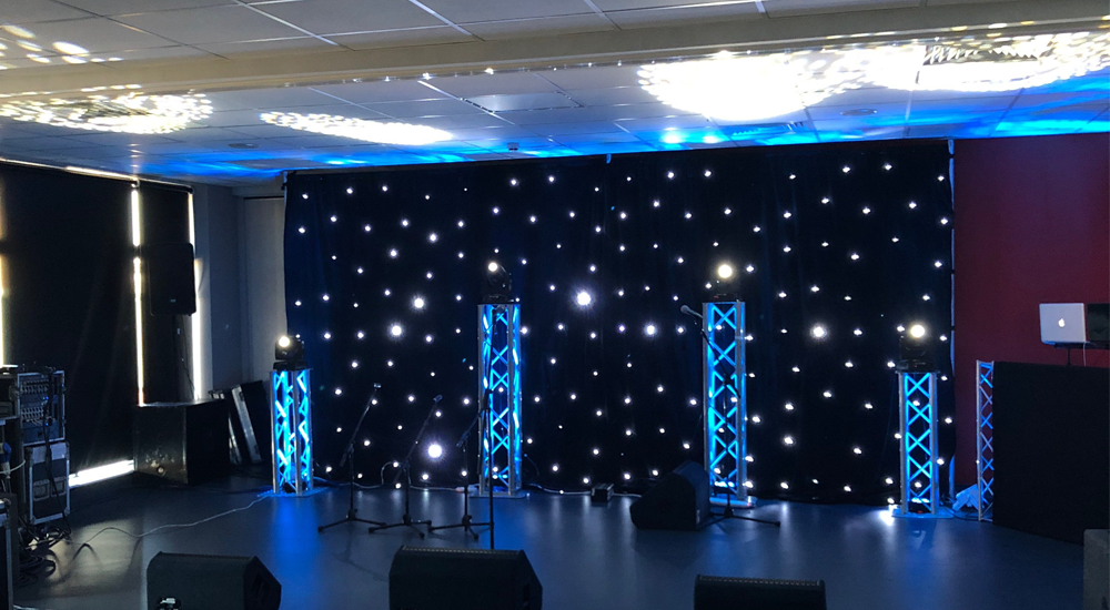 An image of moving head lighting and a lighting backdrop at a party venue.