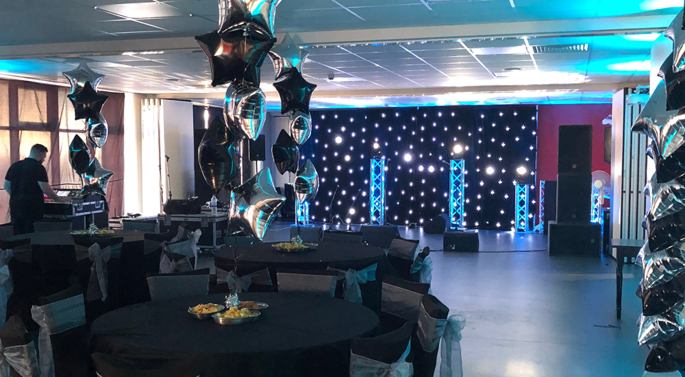 An image of a moving lighting head being at a venue decorated with balloons in the shape of stars, a light up backdrop and various round tables.