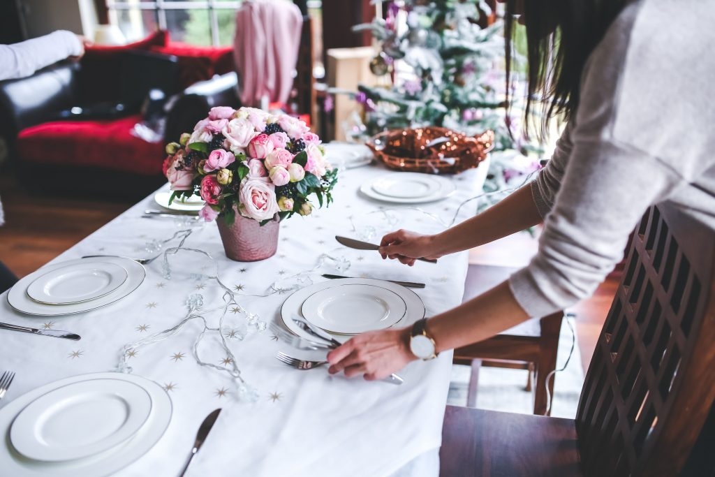 An image of an adult creating a elegant table setting at a wedding reception.