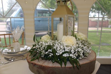 An image of white roses mixed with white wild flowers in a wreath that surrounds a pillar candle inside a lantern at Shearsby Bath.