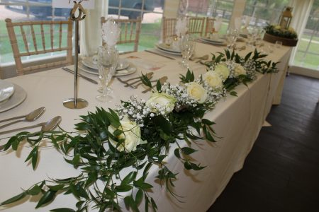 An image of a garland postioned on the top table at a wedding ceremony, mixed with white roses, green leaves and white wild flowers at Shearsby Bath.