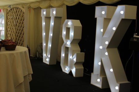 An image of large white light up letters, placed at a wedding reception.