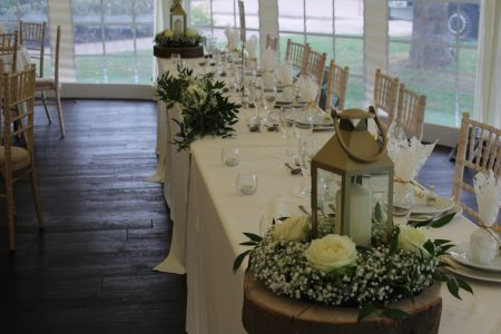 An image of multiple rectangular tables and white wash vintage chairs inside a marquee.