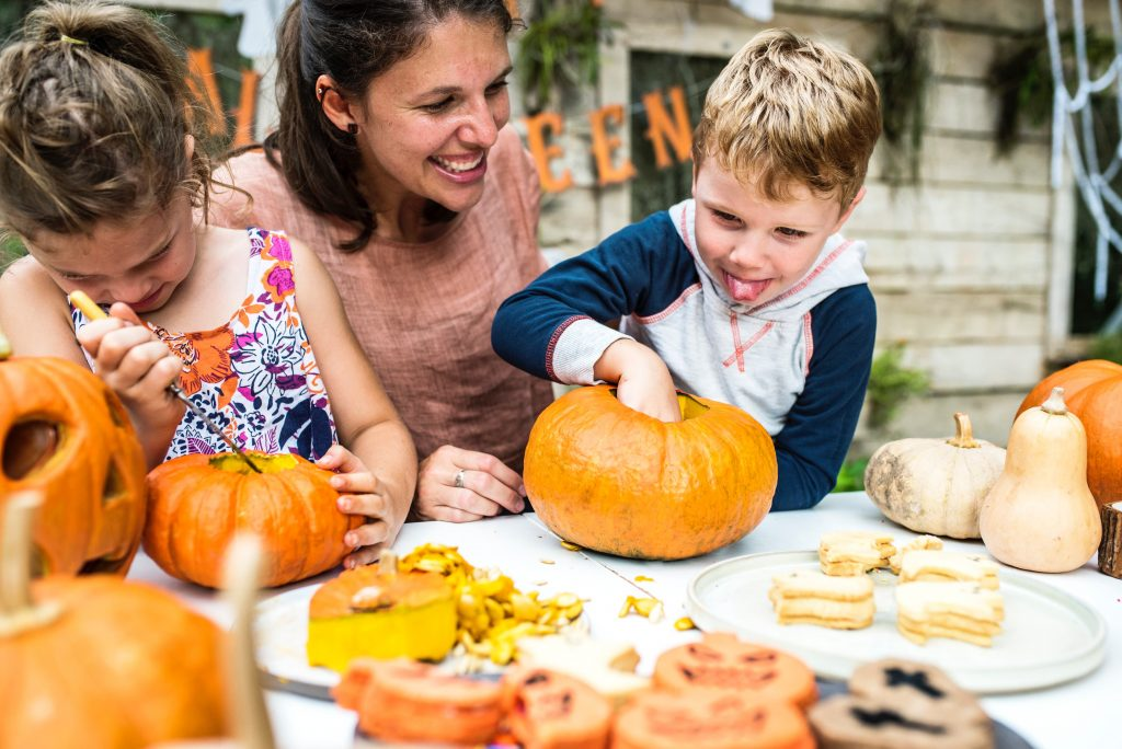 An image of a children carving pumpkins at a Halloween event with their parents.