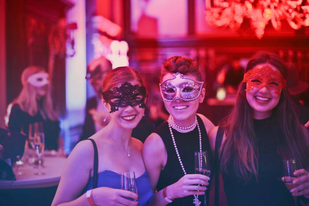 An image of three women in masquerade masks at a Christmas party.